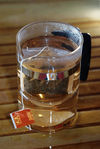 Bag of puerh <span class='translation'>(Pu Er tea)</span> tea brewed in a glass mug