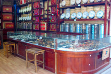 Shop Lijiang, in the foreground and jade jewelry wood in the background puerh <span class='translation'>(Pu Er tea)</span> cakes