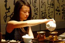 Jeune femme inusant une tasse de puerh