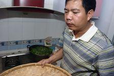 Mr Luo Hou You travaillant des feuilles de thé sans sa cuisine