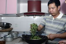 Mr. Luo Hou You working tea leaves freshly purchased in the kitchen