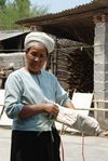 Dai Woman with a series of written Buddhist Dai packed