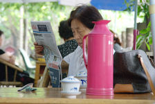 Sichuannaise lisant son journal dans un salon de thé en extérieur